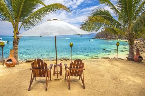 beach chairs and umbrella at the magical las caletas beach hideaway in puerto vallarta mexico