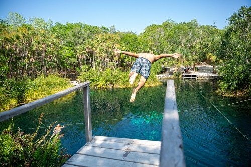 man diving off a wooden board towards a cenote in mexico