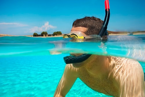 man snorkeling in the waters of aruba
