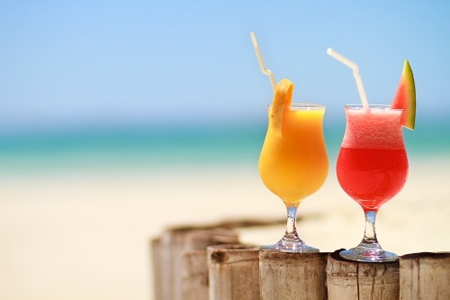 red and orange caribbean cocktails on a wooden fence at the beach