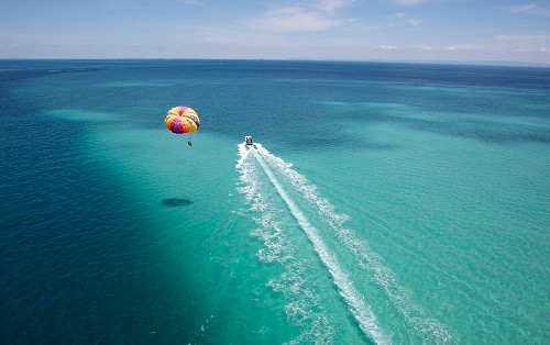 aerial view of couple parasailing on the open mexican waters