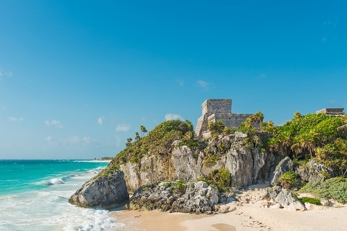 side view of the pyramid of tulum across the beach near cozumel mexico