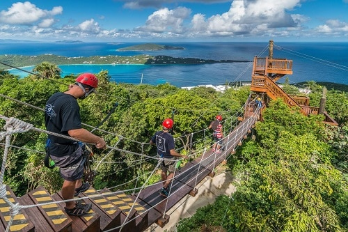 visitors crossing a wooden bridge as the get to a zip line in st thomas
