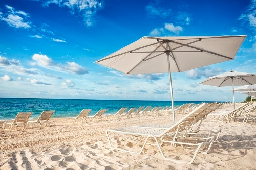 white umbrella and beach chairs on the beautiful sand of lucaya beach in freeport bahamas