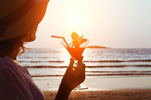 woman holding up her caribbean cocktail as the sun sets
