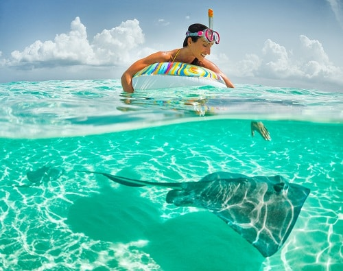 woman with snorkeling gear looking at a stingray swim by