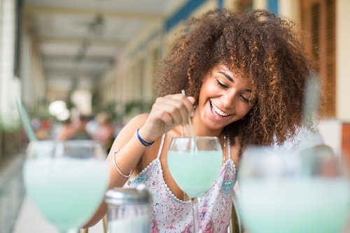 woman smiling as she mixes her light blue cocktail in the caribbean
