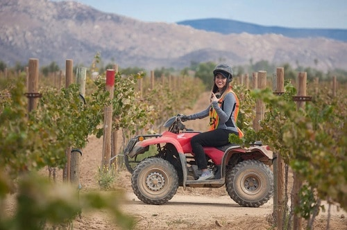 woman smiling as she drives an atv on the wine country of ensenada mexico