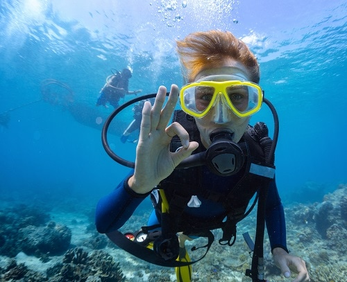 woman waving her hand as she scuba dives off the coast of hawaii