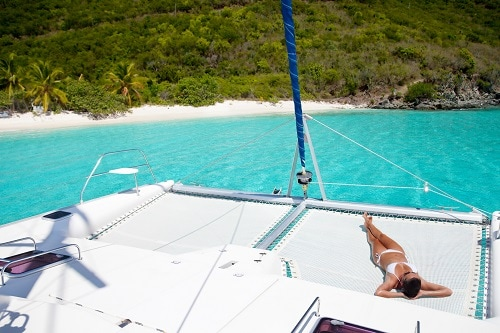 woman sunbathing on a catamaran in amber cove