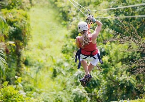 woman zip lining through the canopies of mahogany bay