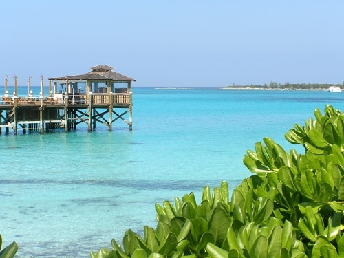wooden pier overlooking the blue clear waters of cable beach in nassau bahamas