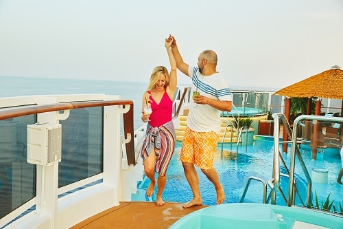 couple dancing on a carnival ship deck as they enjoy their thanksgiving vacation