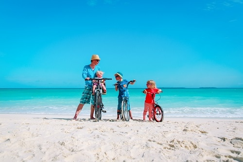 father and his 3 children enjoying a bike ride along the beach in freeport bahamas