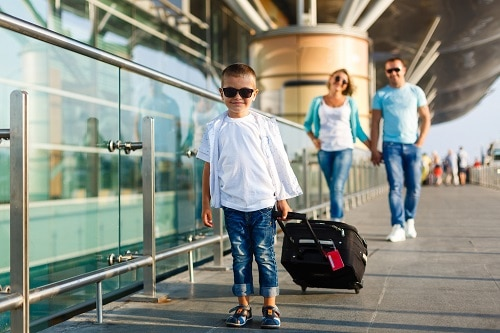 little boy wearing sunglasses leaving the airport with his parents