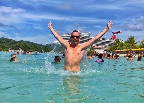 man raising his hands in a western caribbean beach as a carnival ship docks behind him