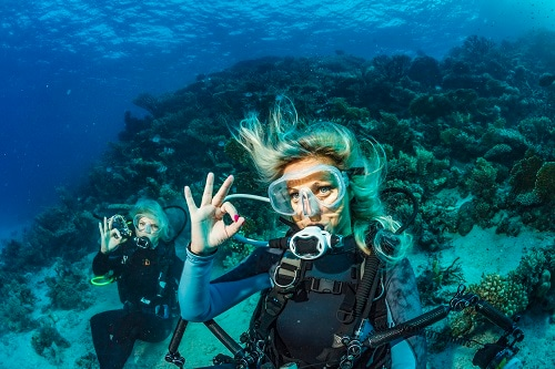 2 woman scuba diving in the deep beautiful waters of the western caribbean