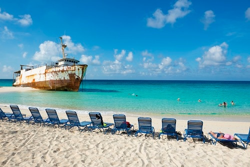 tourists enjoying the beautiful beach of grand turk next to a ship wreck