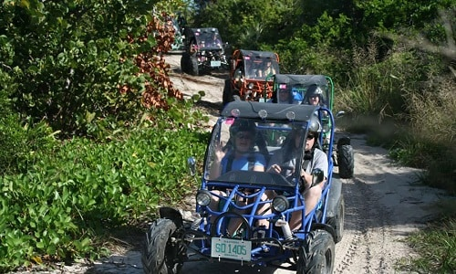 tourists driving on a dune buggy in princess cays bahamas