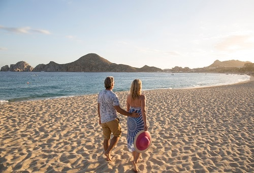 couple walking along the gorgeous beach of cabo san lucas as the sun sets