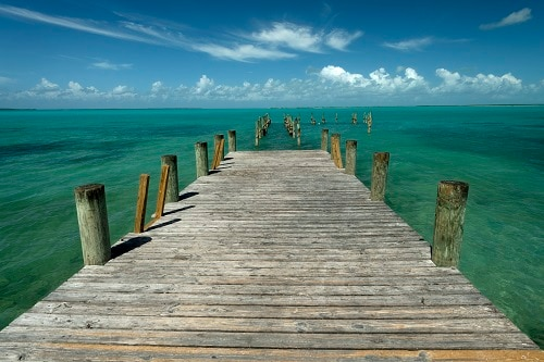 rustic wooden pier along the beautiful beach of princess cays, bahamas