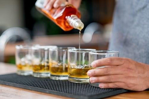 bartender serving spiced rum onboard carnival paradise