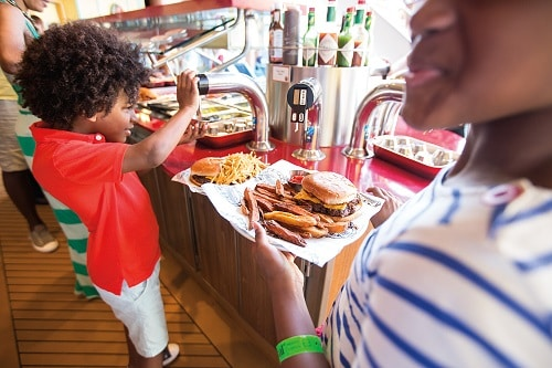 boy adding ketchup to his hamburger from guys burger joint on carnival breeze