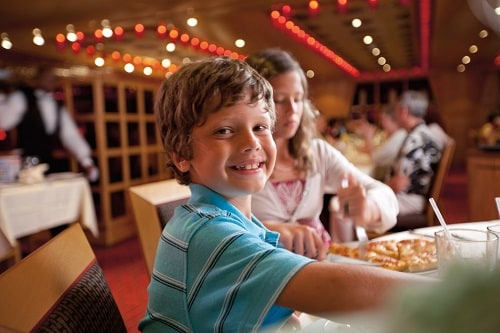 boy eating pizza from carnival magic's pizzeria del capitano with his family