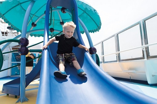 boy sliding down a slide in camp ocean