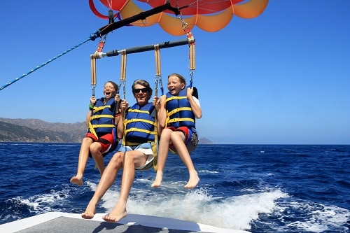 father and his two daughters parasailing in baja mexico