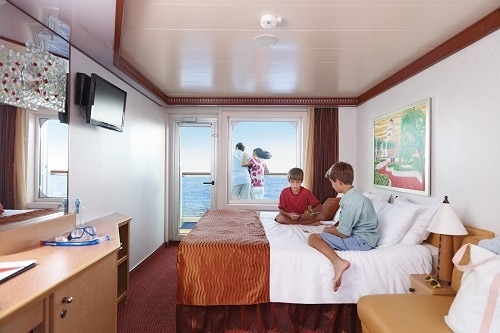 kids playing cards in the family stateroom as their parents enjoy the balcony