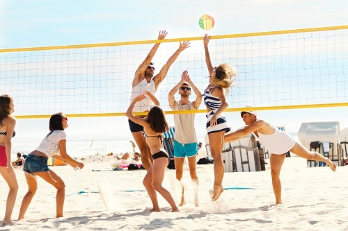 group of friends playing volleyball in a beach resort getaway in mexican riviera