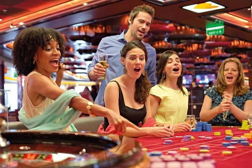 group of friends enjoying a game of roulette on carnival vista's casino