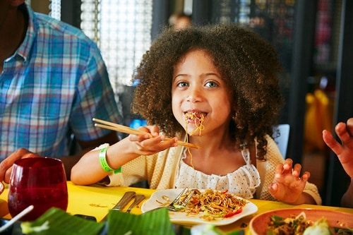 little girl eating chow mein from jiji kitchen on a carnival cruise ship