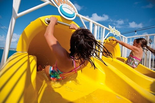 sisters sliding down a water slide on carnival magic's waterworks