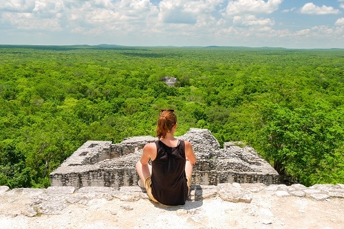 woman enjoying the view of the rainforest on top of a mayan temple in mexico