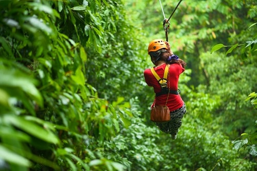 woman zip lining across the canopy in the mexican riviera