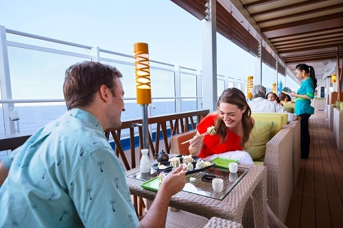 couple eating bonsai sushi with an ocean view onboard carnival vista
