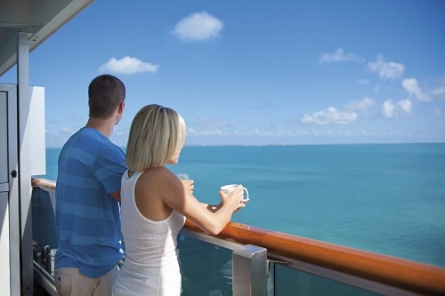 couple enjoying the ocean view from their balcony as they cruise to the bahamas