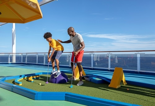 father teaching son how to play mini golf on carnival spirit