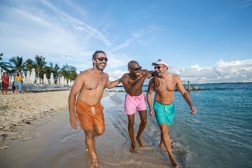 three friends laughing as they walk along the beach in the bahamas