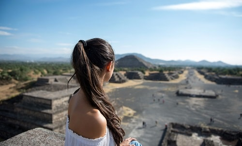 young woman looking over the mayan ruins in mexico