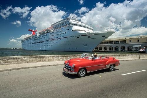 1960s vehicle driving past carnival paradise in havana cuba