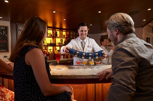 bartender from alchemy bar serving cocktails to a couple onboard carnival sunshine