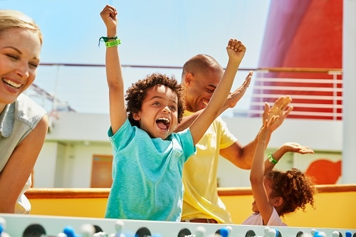 boy celebrating a goal as he plays foosball in carnival vista's sportsquare