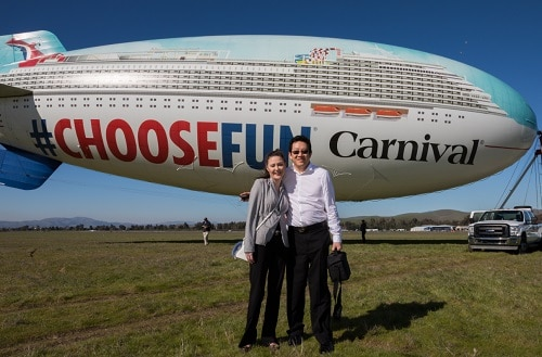 carnival mastercard cardmembers posing in front of the carnival choosefun airship