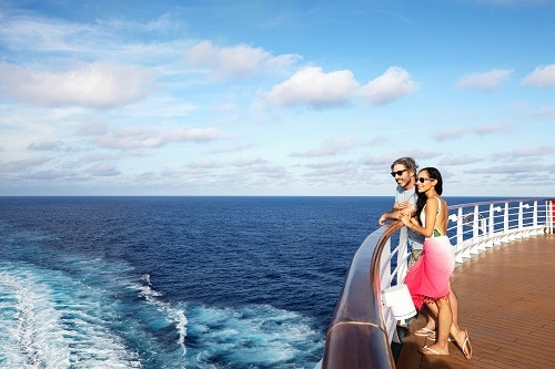 couple looking over the rail of a carnival cruise ship as they cruise the ocean