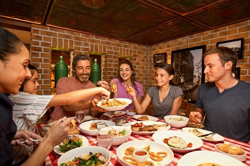 family eating italian food from cucina del capitano onboard a carnival cruise