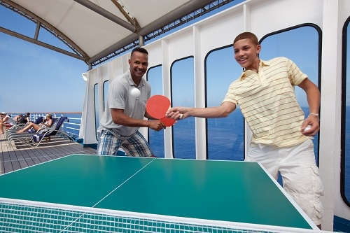 father and son playing ping pong onboard a carnival ship