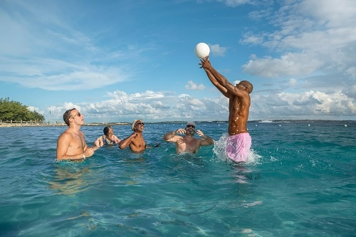 friends playing volleyball in the caribbean sea